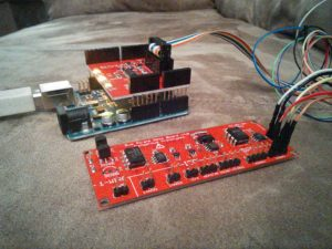 The Bus Pirate Arduino Shield is the shield sitting on top of the Arduino in the background.  The item in front is the Bus Pirate Demo Board that I'm using to test the shield.  There are a few joints that I missed soldering and there are a few missing capacitors.